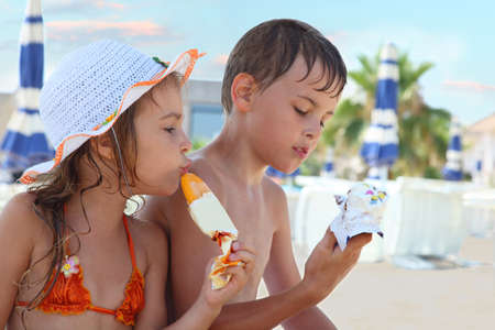 child swimsuit: Brother and little sister eating ice cream after bathing. Girl wearing swimsuit and hat