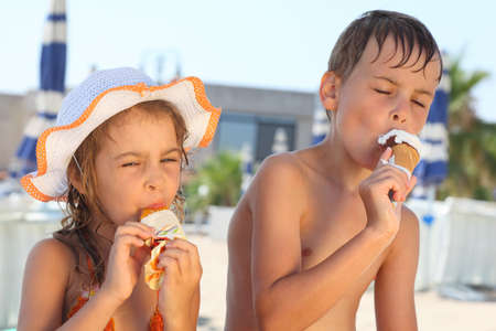little girl swimsuit: Brother and little sister eating ice cream after bathing. Girl wearing swimsuit and hat