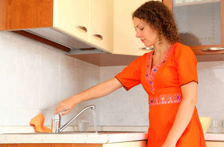 beautiful young woman standing in kitchen. She opens faucet.  photo