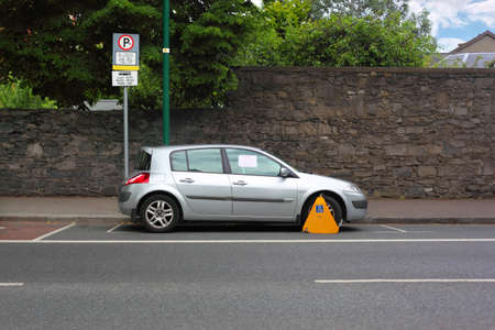 clamped: Car street clamped with yellow metal wheel clamp. Trees grow behind wall  Editorial