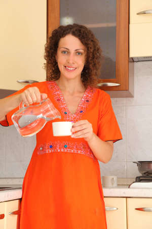 pours: beautiful young woman standing in  kitchen and pours clean water into cup