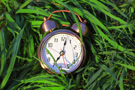 The beautiful classical alarm clock lies on a green grass. Arrows show seven hours. photo