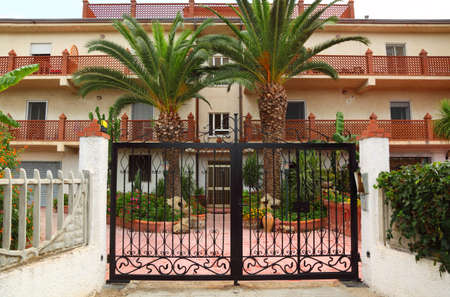 front entry: Forged black gate of sanatorium. palm trees and buildings of sanatorium can be seen outside gates