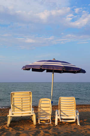 MANDATORICCIO, ITALY – JULE 20: Three lounge chairs for family on beach. Mother, father, child on Jule 20, 2010 in Mandatoriccio, Calabria, Italy. Calabria region visited annually by only 3% of Italy's 45 million tourists  photo