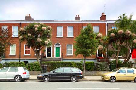 parked: cars parked near two-story red brick house on street in Dublin, Ireland