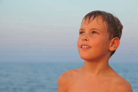 head of little boy after swimming is on seashore. his hair is wet