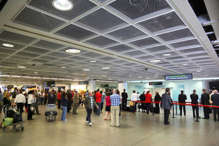 People waiting board to airplane in hall of Dublin airport, Ireland