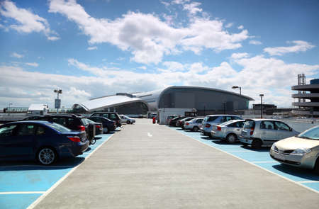many cars are parked. blue sky and white clouds. very good weather