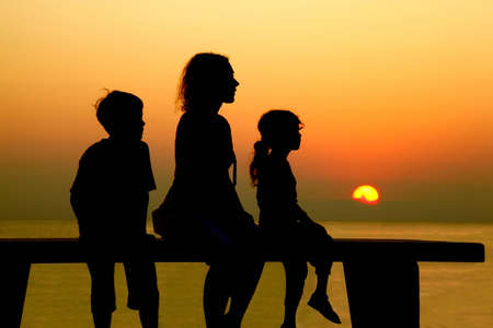 Mother with two children sits on  bench and looks at  beach toward sunset photo