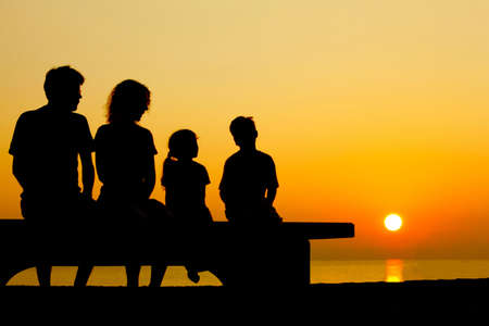 Father with mother and two children  sit on  bench on  beach in  evening and converse photo