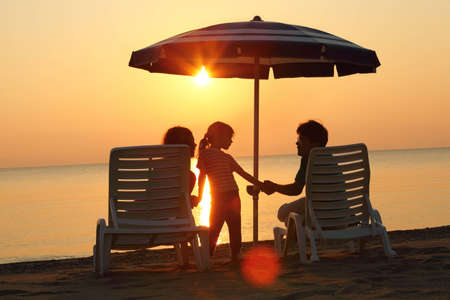 Mother and father sit on  beach in  evening under  umbrella and hold daughter on hands photo