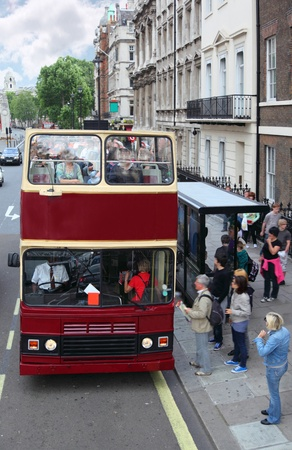public service: Red double-deckers with tourists on street of London, England. People come in red double-decker.