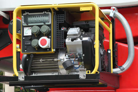 Black panel with petrol compact electricity generator inside red fire engine