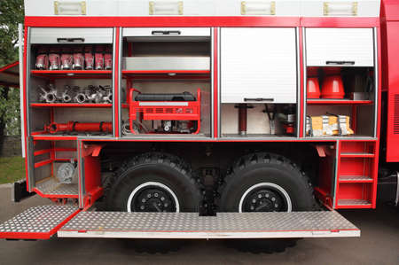 deployed: Open big red fire engine equipped with fire cocks and hoses at day