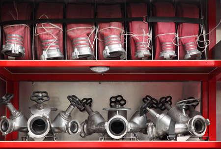 voiture de pompiers: Bouches et tuyaux précis organisés à l'intérieur du moteur au feu rouge grande Éditoriale