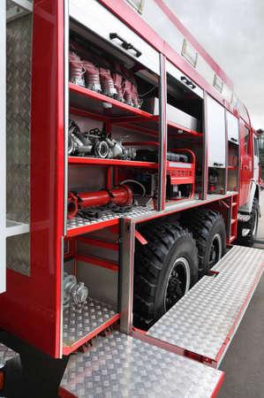 voiture de pompiers: Bouches et tuyaux équipés à l'intérieur du moteur au feu rouge grande au jour Éditoriale