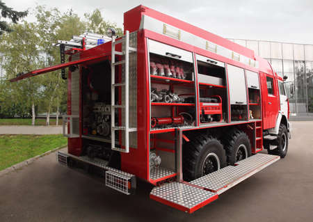 deployed: Side view of fire cocks and hoses equipped inside big red fire engine at day Editorial