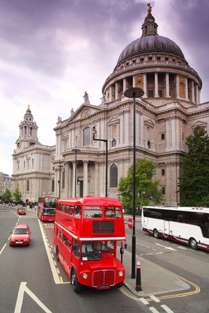 St. Pauls Cathedral and red double-deckers with tourists in London