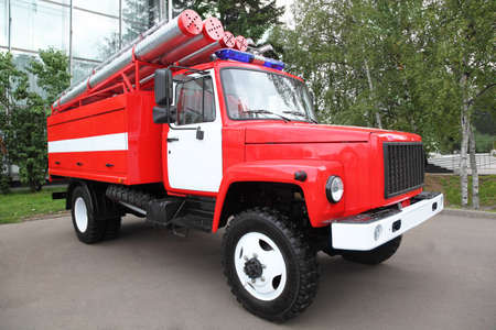 deployed: Big red fire engine with pipes and flasher on the roof at summer day Editorial
