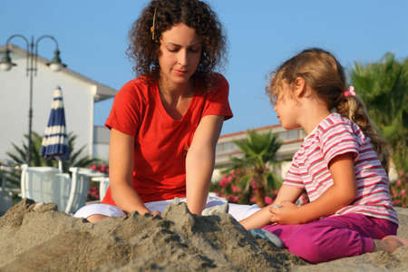 mandatoriccio: Mother with daughter sit on  beach in  day-time and play on sand