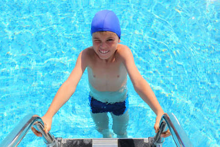 Boy in dark blue little cap entering in water in  pool photo