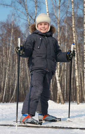 Young boy stands on cross-country skis inside winter forest at sunny day photo