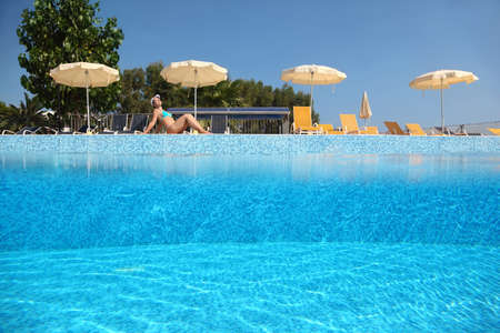 mandatoriccio: Woman becomes tanned near  pool under open-skies in  day-time near deck-chairs and umbrellas, underwater half photo Editorial