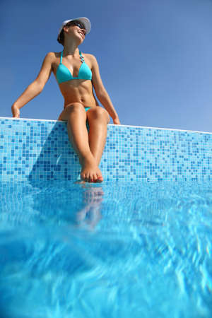 Woman in  blue swimming suit sits on verge of pool and becomes tanned, underwater package shot photo