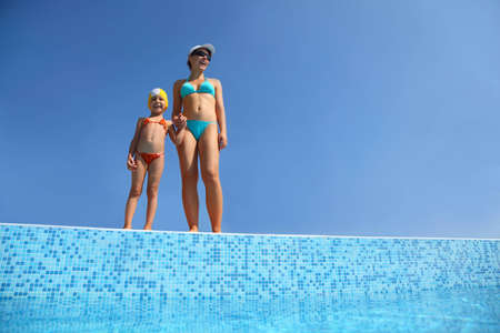 Girl with  mother stand on skirting of pool under open-skies and become tanned, underwater package shot photo