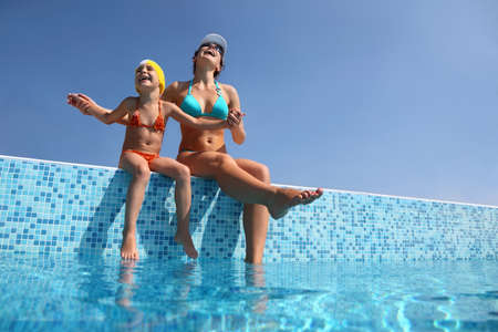 gladly: Mother with daughter sit on  parapet of pool and gladly lift  head to sky Stock Photo