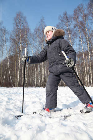 Young happy boy skates on cross-country skis with poles inside winter forest at sunny day photo
