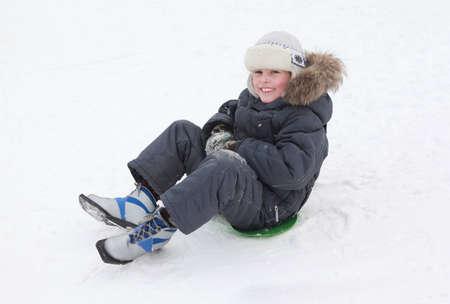 ni�o en patines: J�venes sonrientes patines de hielo del muchacho en verde-barco en pura nieve blanca