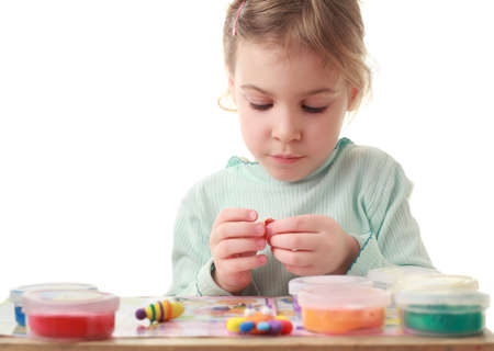 Little girl sitting at table and carefully sculpts figures makes of plasticine Stock Photo - 12614832