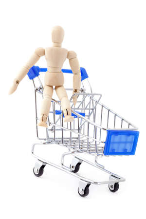 mart: Shopping concept. Wooden doll sitting in the metal shopping cart.