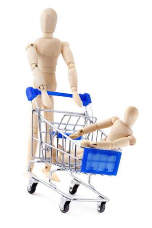 family mart: Shopping concetto. Un manichino di legno rotola un altro nel carrello.