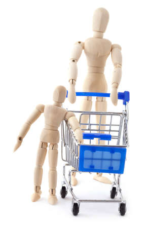 layman: Family shopping concept. Wooden dolls family go to the supermarket with metal shopping cart.