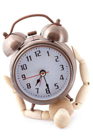 layman: Wooden dummy crushed by old-styled metal alarm clock.