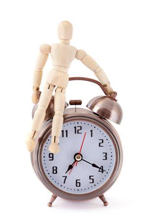 layman: Wooden dummy sitting on old-styled metal alarm clock.