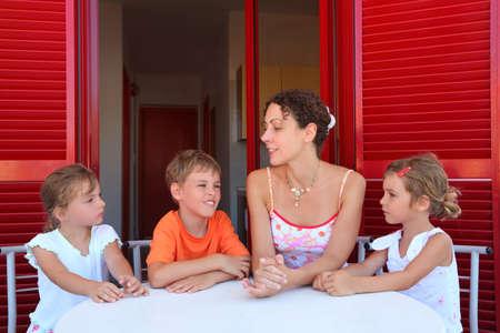 mandatoriccio: Three children and mother sit on  verandah  round table near doors and speak