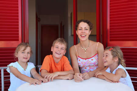 verandah: Woman with three children sits in  number on  verandah   table with  white table-cloth and laughs