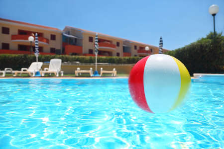 mandatoriccio: An inflatable ball lies in  pool under open-skies near cottages, underwater package