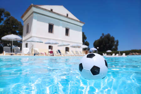accent: Soccer ball lies in water in  day-time in  pool under open-skies Editorial