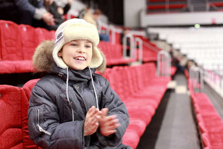 admirers: Boy with  delight claps ones hands on  hockey match Stock Photo