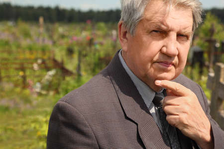 old serious senior in grey suit standing on cemetery, hand on chin, sunny summer photo
