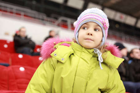 Girl looks after  game of favourite hockey command with interest