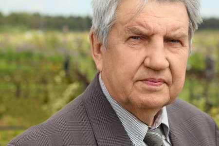 portrait of old serious senior in grey suit standing on cemetery, looking at camera, summer photo