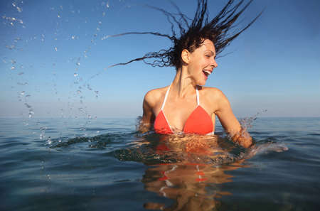 emerge: Young beautiful woman wearing red bathing suit spinning in sea. drops from her hair. from the underwater package Stock Photo