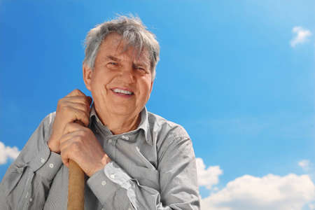 shove: old senior in striped shirt with shove smiling and looking at camera, blue sky with clouds