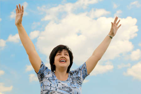 brunette plumpy mature woman smiling, hands up, blue sky and clouds photo
