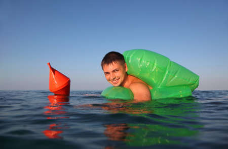 floats:  young man swims in sea on green lifeline. orange anchor buoy floats on sea. Stock Photo